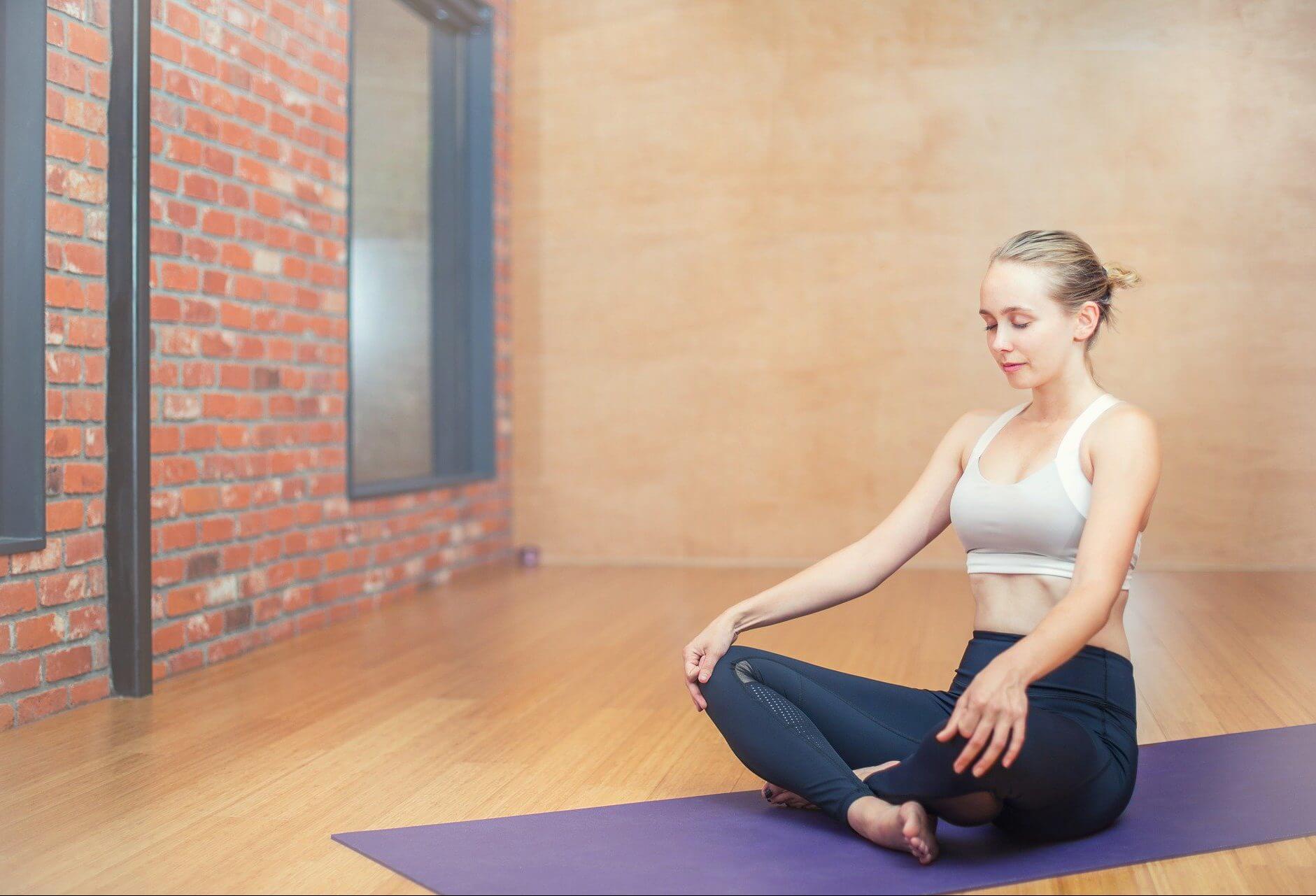 Frau macht Atemtherapie auf einer Gymnastikmatte